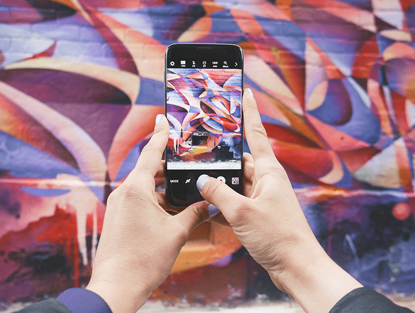 Smartphone against mural on a wall